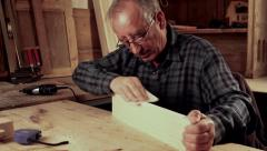 Senior carpenter sending piece of timber with sandpaper Stock Footage