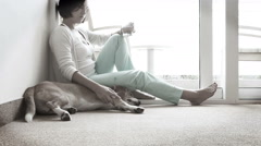Sad woman siting on the floor near the friendly dog - stock footage