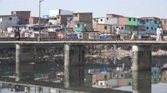 India, Mumbai, people cross a bridge in a slum area Stock Footage