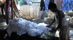India, Mumbai, a worker cleans clothing by hand in Dhobi ghats Stock Footage