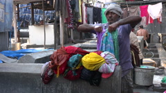 India, Mumbai, a worker cleans colorful dresses inside the Dhobi ghats - stock footage