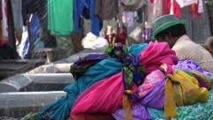 India, Mumbai, worker cleaning colorful dresses, saris, in the Dhobi ghat - stock footage