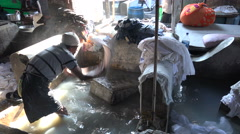 India, Mumbai, worker beats dirt out of clothing, cleaning process, manual labor - stock footage