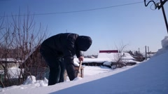 Man removing snow from a roof with a snow shovel Stock Footage