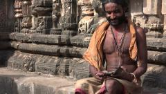 India technology contrast, religious guru uses modern smartphone in temple Stock Footage