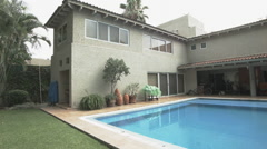 Establishing shot of a modern colonial style house with a pool Stock Footage