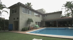 Establishing shot of a modern colonial style house with a pool - stock footage