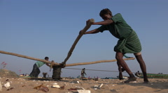 Traditional fishing village, men at work heavy labor at beach in India Stock Footage
