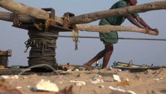 Asian fishermen pull in their wooden fishing boats on the beach in India Stock Footage