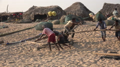 Traditional fishing community, labor, workers, pushing, beach, India Stock Footage