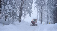 Stock Video Footage of Crawler Snowplow Cleans Snow from Road in the Woods