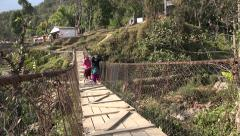 Nepal, village scene, women carry baskets with plastic bottles over footbridge Stock Footage