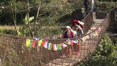Women carry baskets over a wooden footbridge in Nepal Stock Footage