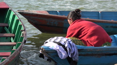 A woman washes clothing at Phewa lake in Pokhara, Nepal Stock Footage