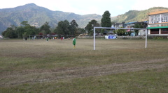 Young men play soccer on a pitch in Pokhara, Nepal Stock Footage