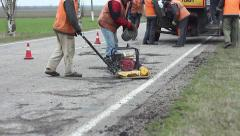 Road resurfacing after winter. Plugging cracks, pits, potholes road services  Stock Footage
