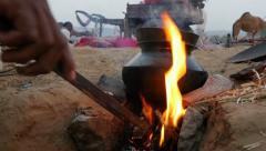 Cooking food on open stove in desert camp in India Stock Footage