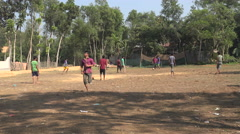 Young men play soccer (football) on a field in rural Bangladesh Stock Footage