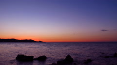 Red sunset with blue sky by the sea - time lapse Stock Footage