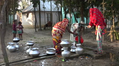 Village scene in Bangladesh, women use a water pump Stock Footage
