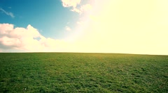 Man walking on the edge of a green hill with beautiful clouds above Stock Footage