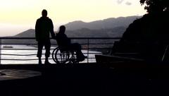 Man on wheelchair watching the island and ocean during the sunset Stock Footage