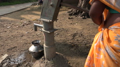 India, a woman operates a water pump in a small village Stock Footage
