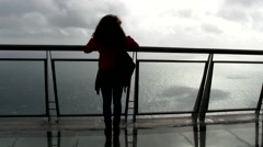 Woman looking at the Atlantic ocean in a windy weather. Stock Footage