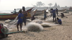 India fishermen, beach community in small village with temple in background - stock footage