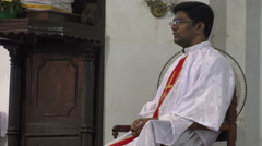 An Indian priest waiting to give a speech inside a church Stock Footage
