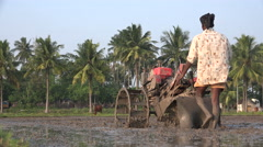 Indian farmer uses machine to plow a paddy field - stock footage