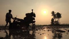 Silhouette of Asian farmer plowing a paddy field in India Stock Footage