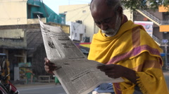India, a religious man reads a newspaper in the morning Stock Footage