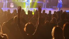 Audience cheerfully applauds clapping hands at the concert flashing spotlight Stock Footage
