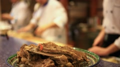 Boiled meat ribs on plate in the foreground and chefs prepare asian food Stock Footage
