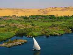 Boat, felucca, on the Nile river with sand dunes - stock photo