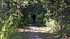 Man walking forward on footpath in shade Stock Footage