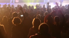 Audience cheerfully applauds clapping hands at the concert flashing spotlight - stock footage