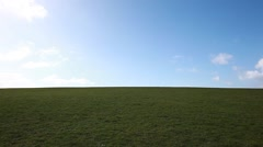Man walking on the edge of a green hill with beautiful clouds above, Stock Footage
