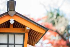 Japanese style house shaped lamp with colorful autumn leaves Stock Photos