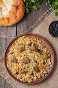 Plate of pilaf, traditional turkish spicy food with rice, fried meat, carrot - stock photo