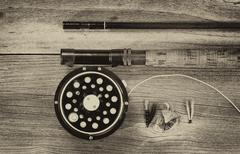 Vintage fly reel and rod on aged wood - stock photo