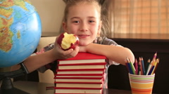 Elementary age girl posing on a stack of books. - stock footage