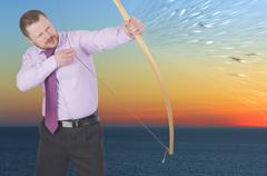 Businessman practicing archery on sunset background Stock Photos