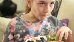 Little girl eating dryed fruit Stock Footage