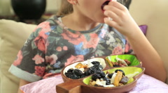 Little girl eating dried fruit Stock Footage
