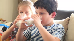 Happy little boy and girl drinking a glass of milk Stock Footage