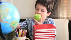 Elementary age boy posing on a stack of books. - stock footage