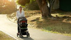 Woman Mother Mom With Toddler in Pushchair Walking In Park Stock Photos