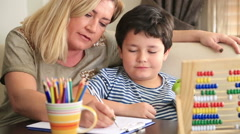 Little student doing homework with his mother Stock Footage